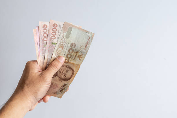 thai money in the hand on white table background – zdjęcie