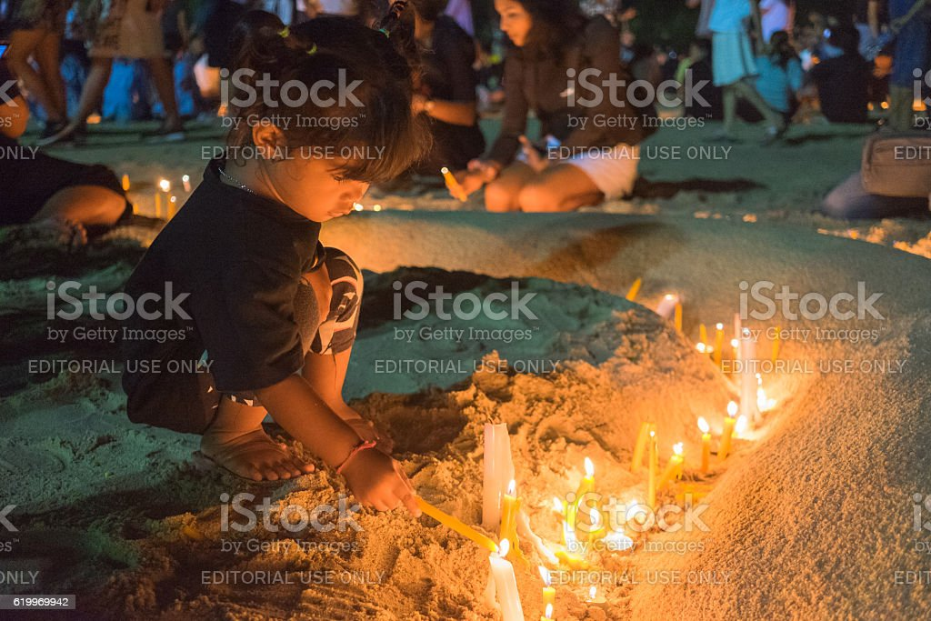 Thai mourners hold candles for the late King Bhumibol stock photo