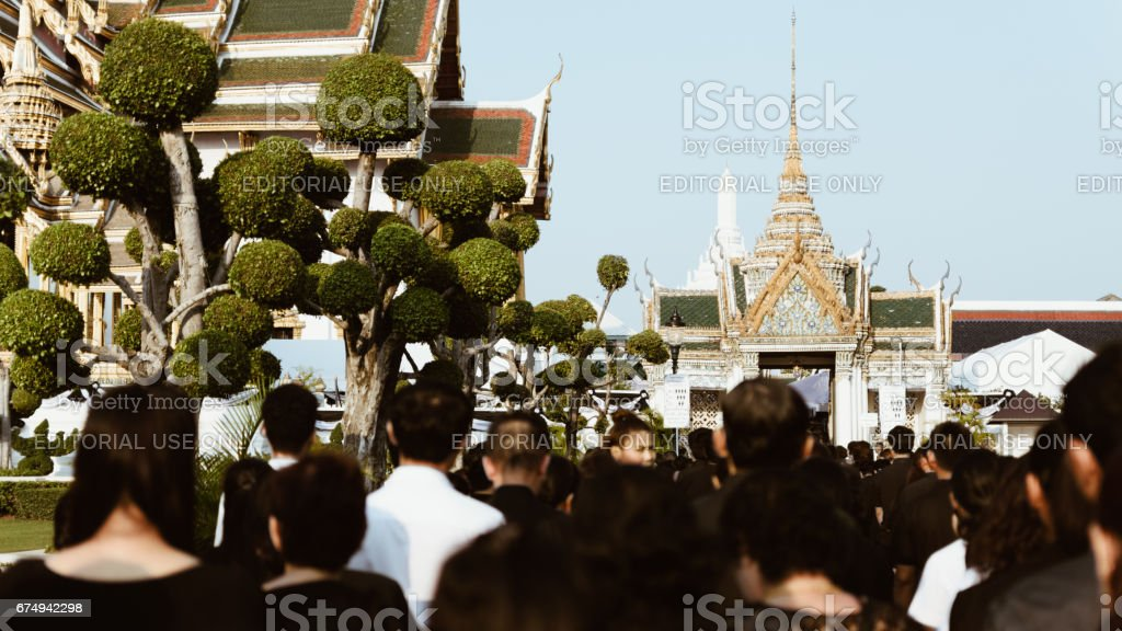 Thai mourners wearing black color waiting in The Grand Palace to pay tribute and respect to their beloved Rama 9 Thai King Bhumibol Adulyadej stock photo