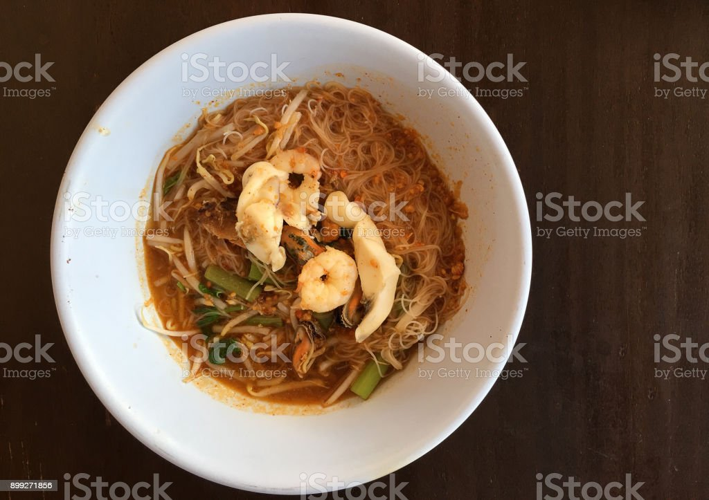 Thai noodle Tom Yum, spicy seafood noodles soup in a bowl on rustic wooden table, Traditional Thai style food stock photo