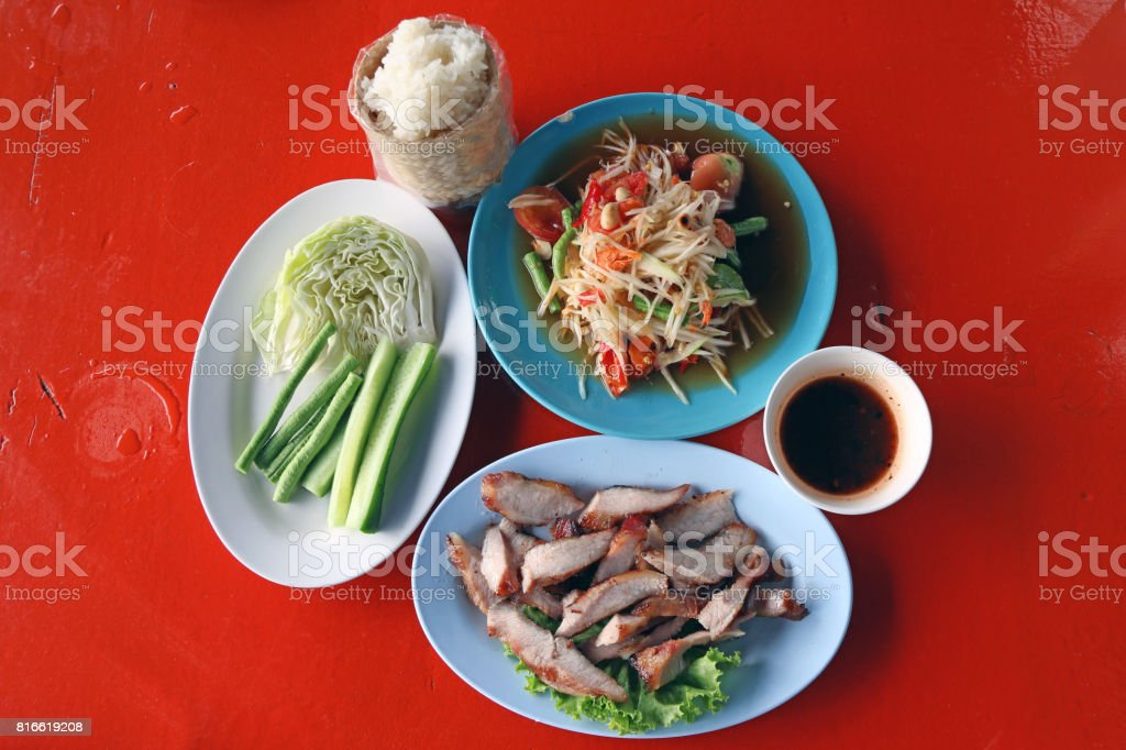 Thai Northeastern food set, which consists of papaya salad, Grilled Pork and sauce, Sticky rice in the wicker and Vegetable (cabbage, Long bean, cucumber) on the red table. stock photo