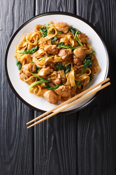 Thai Pad See Ew noodles with chicken, Chinese broccoli and egg close-up on a plate. Vertical top view stock photo