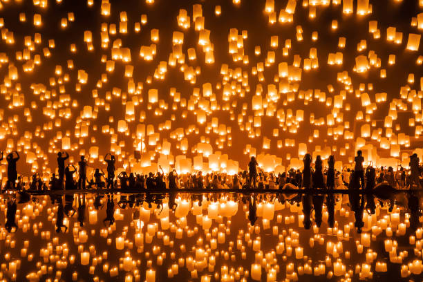Thai people release sky floating lanterns or lamp to worship Buddha's relics with reflection. Traditional festival in Chiang mai, Thailand. Loy krathong and Yi Peng Lanna ceremony. Celebration. stock photo
