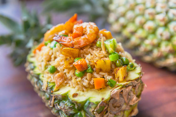 Thai pineapple fried rice Close up Thai pineapple fried rice with shrimp, chicken meat and vegetables slices. fried rice stock pictures, royalty-free photos & images