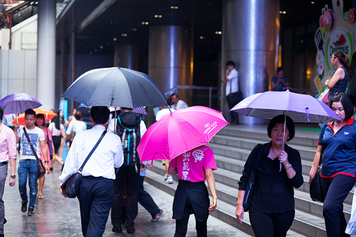 Thai pople with umbrellas at rainy day in Silom Road