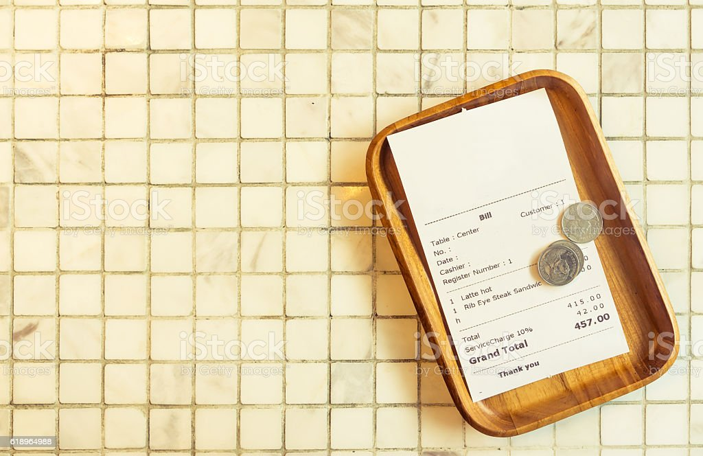 Thai restaurant bill payment receipt on white marble tile table stock photo