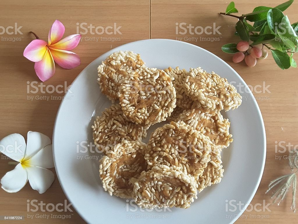 Thai rice biscuit on plate, flowers frangipani on table стоковое фото