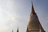 Round big pagoda with smaller ones around. Shot during sunset at a Thai temple, Wat Prayoonwongsawat, in Bangkok, Thailand.
