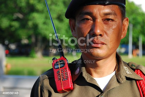Bangkok, Thailand - June 10, 2007: A Thai security guard at Lumphini Park, a large and popular park in downtown Bangkok. A Motorola communications device is at his shoulder.