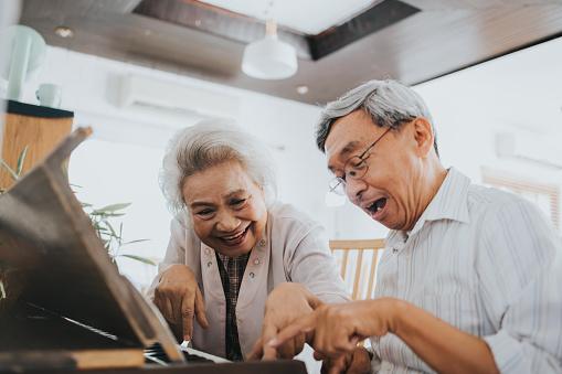 Thai senior couple enjoy playing paino at home