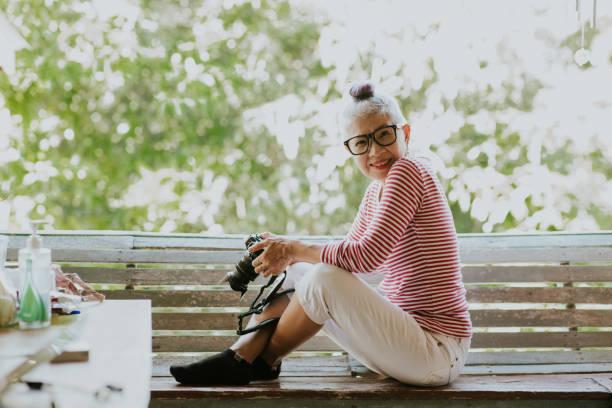 自宅で検疫しながら、彼女の愛の趣味を持つタイのシニアヒップスターの女性 - showus ストックフォトと画像