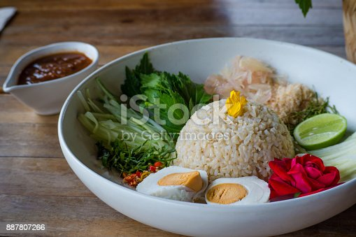 Thai Southern Spicy Rice Salad with Vegetables,herbs and egg on wooden table.