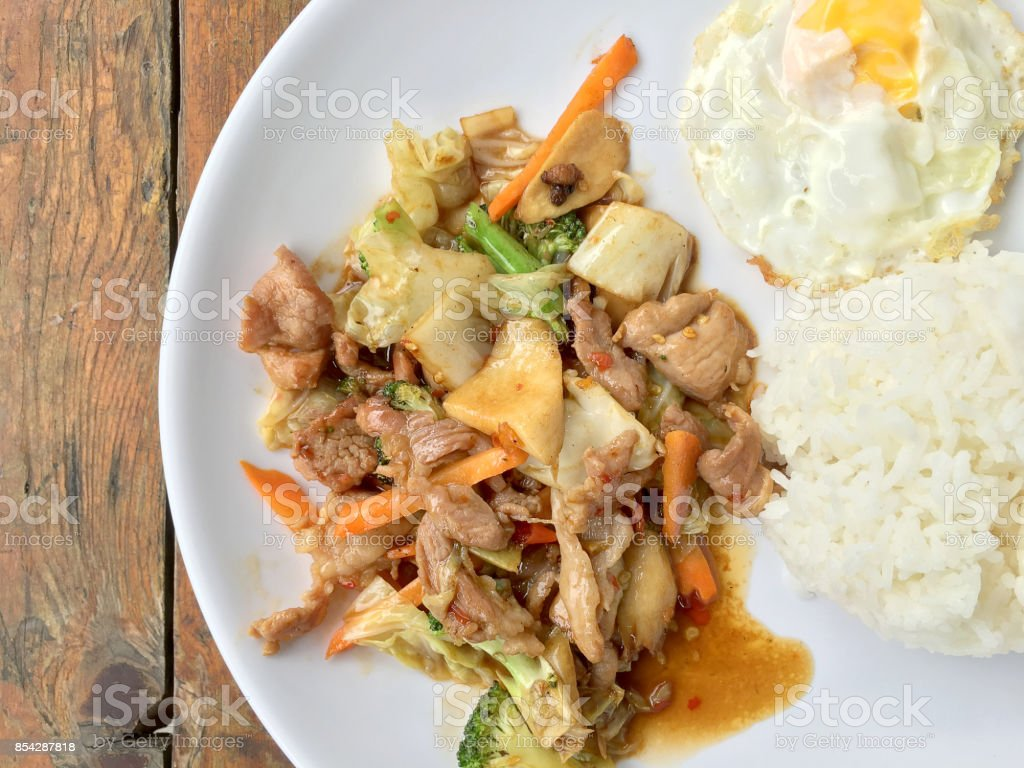 Thai spicy food : A plate of pork stir fry with vegetables and fried egg with rice in white dish on wooden table.  healthy dish. stock photo
