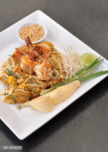 istock Thai stir-fried vermicelli noodles with shrimps (Pad Thai) served on brown background 1311514232