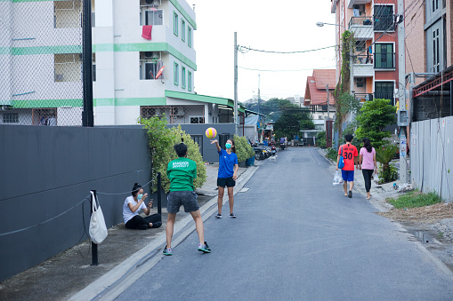 Thai students are playing with volleyball as leisure activity in street in residential district of Ladprao / Ratchada. A woman is sitting on street. Some pedestrians are walking in right background