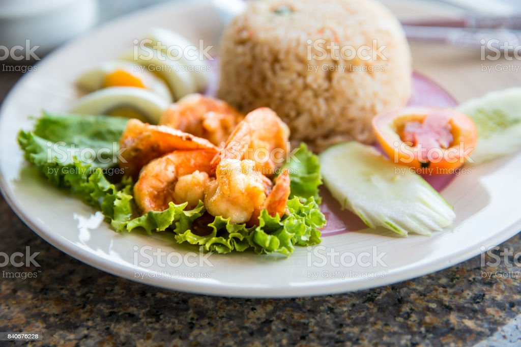 Thai style cuisine fried rice with shrimp and egg,Woman eating boiled shrimp with fry rice and boil egg, Concept of healhty food or cuisine stock photo