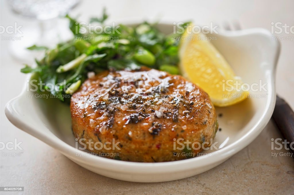 Thai style fishcakes with spicy soy glaze, green salad and lemon wedge stock photo