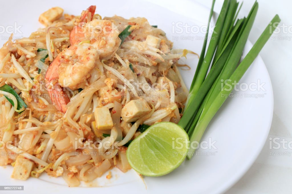 Thai style noodles, Pad Thai, stir-fried rice noodles with shrimp serve with vegetable in white plate on white background. The one of Thailand's national main dish. the popular food in Thailand. zbiór zdjęć royalty-free