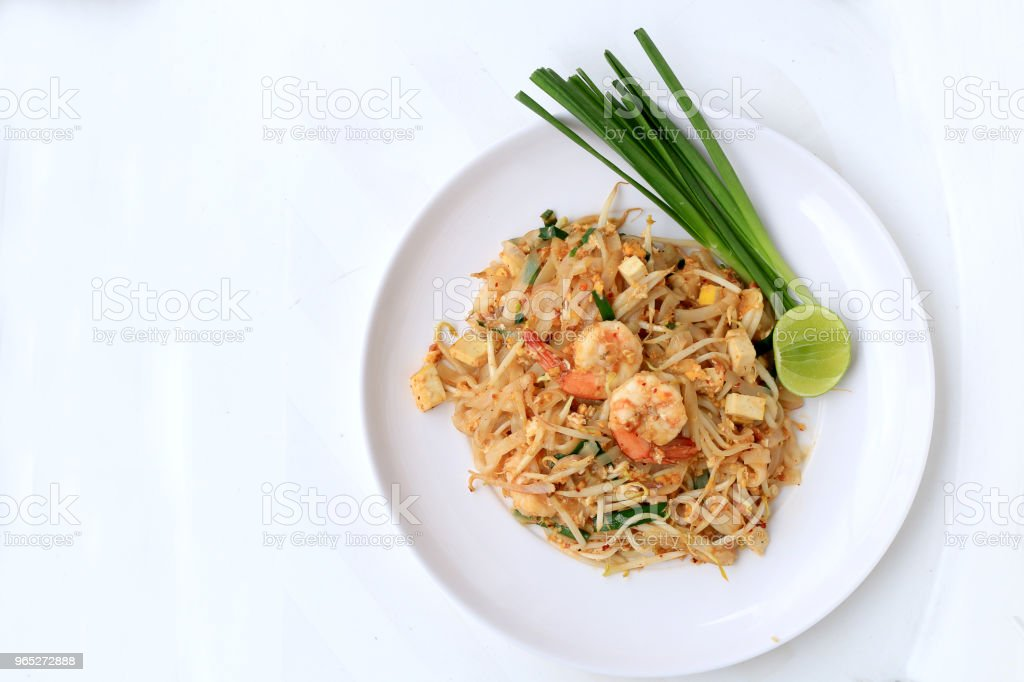 Thai style noodles, Pad Thai, stir-fried rice noodles with shrimp serve with vegetable in white plate on white background. The one of Thailand's national main dish. the popular food in Thailand. royalty-free stock photo