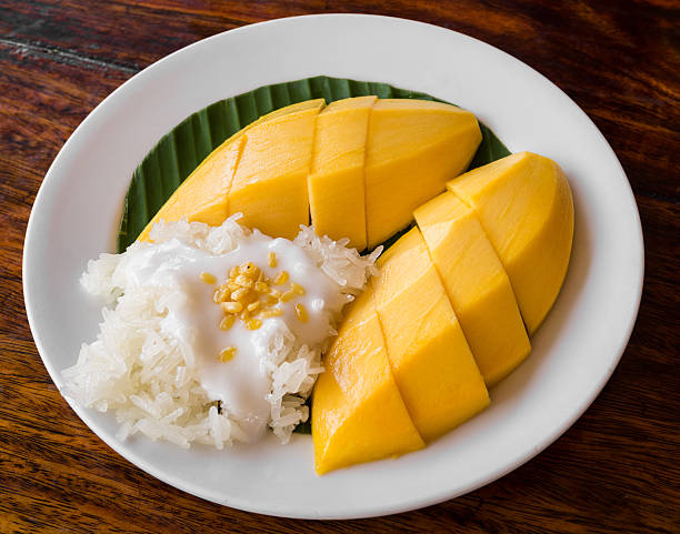 thai style tropical dessert, glutinous rice eat with mangoes - sticky stock pictures, royalty-free photos & images