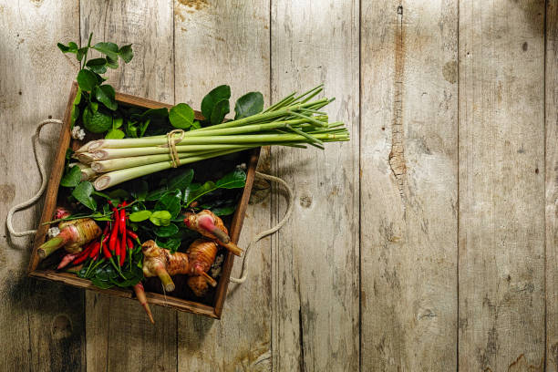 Thai Tom Yam herbs and spices on an old wooden tray sitting on a worn wooden table. stock photo