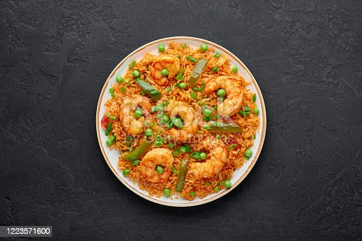 Thai Tom Yum Fried Rice or Prawn Biryani in white plate on black slate backdrop. Tom Yum Fried Rice is Thailand cuisine dish with jasmine rice, shrimps and vegetables. Thai Food. Copy space. Top view