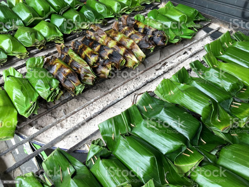 Thai traditional desserts, Thailand dessert wrapped in banana leaves, coconut milk custard with coconut sweet on the stove for cooking, Thai grilled sticky rice on a grilled, street food stock photo