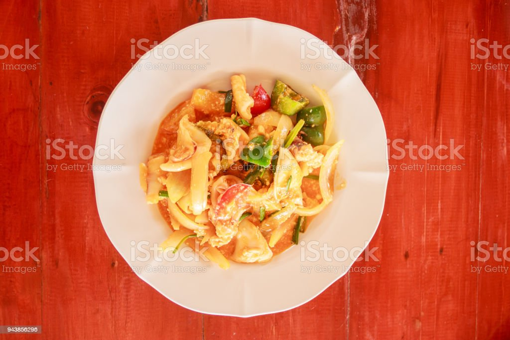 Thai traditional food, Stir fried squid with salted egg on wooden table background. stock photo
