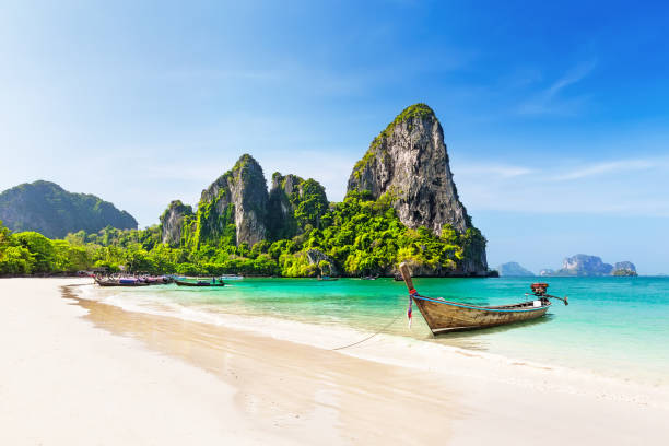 Thai traditional wooden longtail boat and beautiful sand beach. stock photo