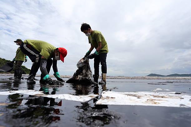 thai volunteers have cleaned oil stains - newspaper beach stockfoto's en -beelden