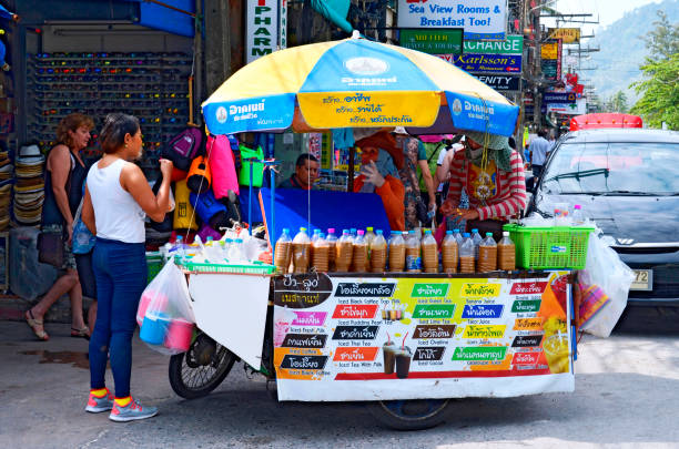 Thai woman buying an iced drink at a stall with two vendors in Patong Beach stock photo