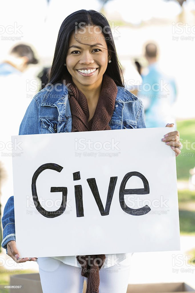 Thai woman holding ''give'' sign at donation event royalty-free stock photo