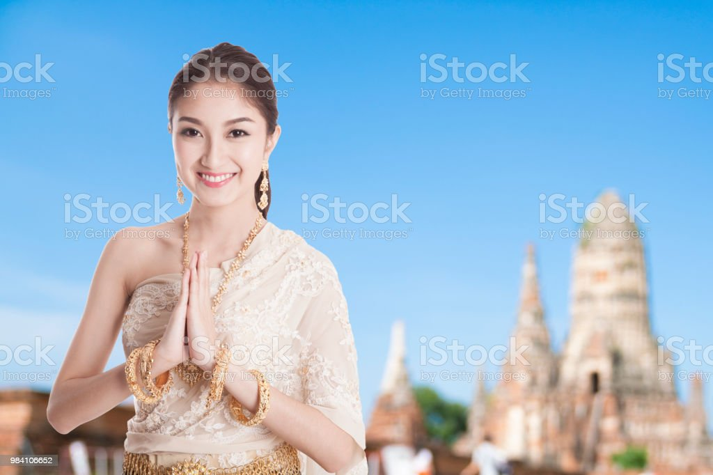 Thai woman in thai dress costume traditional in a welcome pose hello thai woman in thai dress costume traditional in a welcome pose hello sawadee with temple m4hsunfo