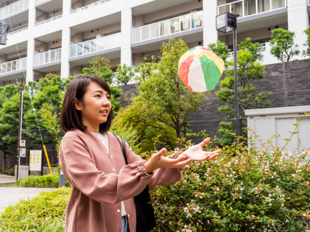 A Thai woman plays with a paper bowl in a residential area of Tokyo. stock photo