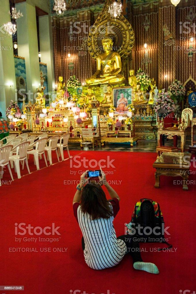 Thai woman praying and taking photo of Buddha stock photo