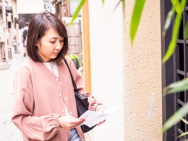 Thai woman reading travel book in Tokyo. stock photo