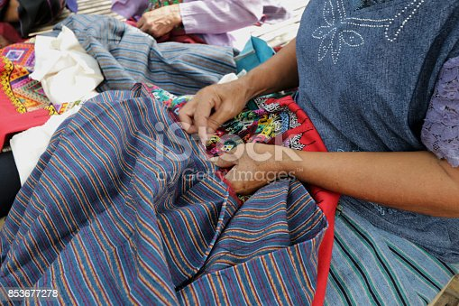 A Thai woman sewing native traditional handmade clothing in Northern Thailand. This antique fabric can be a great gift for dressing and collecting.