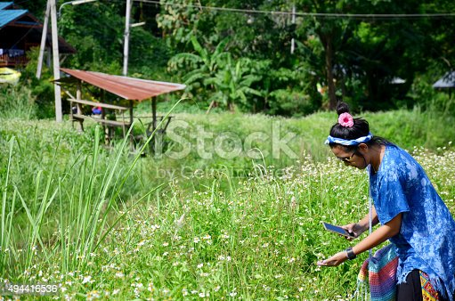 Thai woman use smart phone take photo view of Baan Natong village on wooden bamboo bridge in Phare, Thailand.