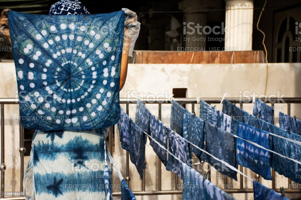 Thai women working Indigenous knowledge of thailand tie batik dyeing indigo color on top of house in Nonthaburi, Thailand stock photo