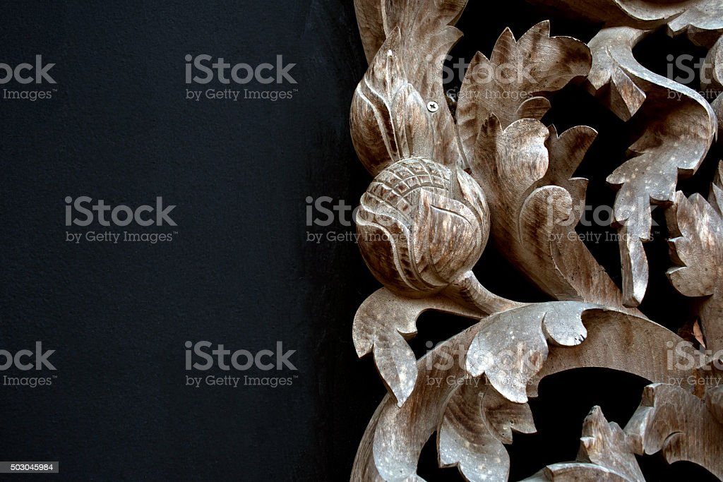Thai wood carving of flowers on a black background stock photo