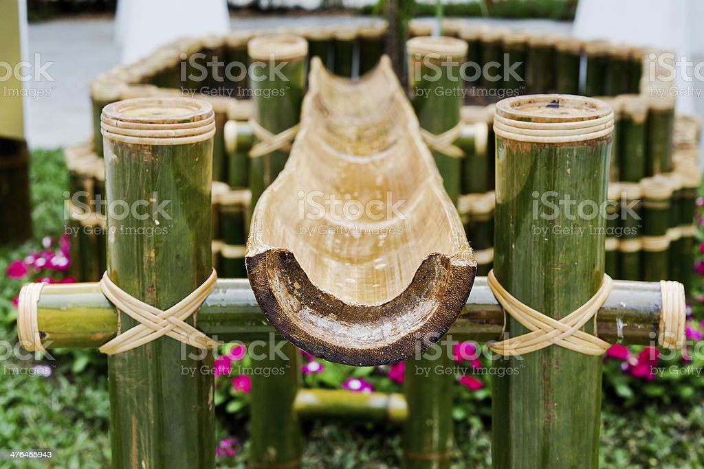 Thailand bamboo fountain with water dripping from snout stock photo