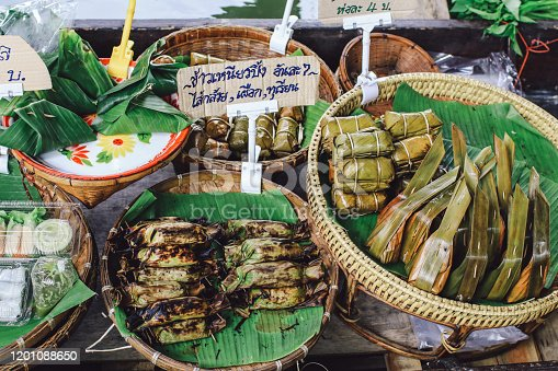 Thailand floating market.Row of grilled coconut sticky rice with varieties of filling such as, banana, taro, etc. wrapped in banana leaves. Thai snack/dessert.