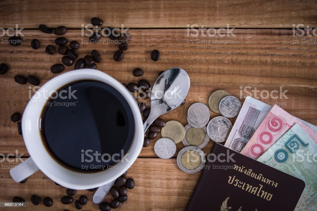 Thailand Passport with currency , Coffee and Glasses on a Wood Background. stock photo