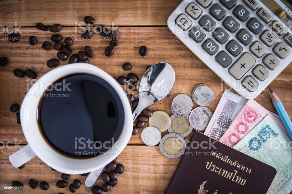 Thailand Passport with currency , Coffee and Glasses on a Wood Background. ロイヤリティフリーストックフォト