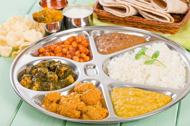 Thali with rice and vegetables on green painted wooden table South Asian selection of vegetarian curries served in a traditional dish with rice, chapatis, poppadoms, yoghurt and chili sauce. dal makhani stock pictures, royalty-free photos & images
