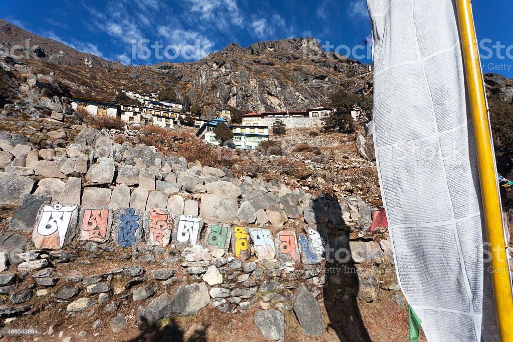 Thame gompa with prayer flags and buddhist symbols stock photo