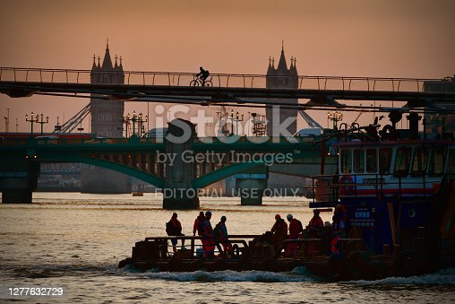Early morning London construction workers travel by boat and a commuter cycles across the  River Thames footbridge silhouetted against the warm dawn sunshine. View from the Embankment under and framing Blackfriars Railway bridge arch