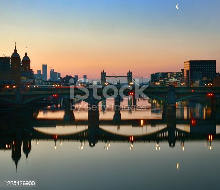 London reflections and crescent moon at dawn. The absence of Thames river traffic during the Covid19 Lock-down Southwark Bridge looking towards Tower Bridge