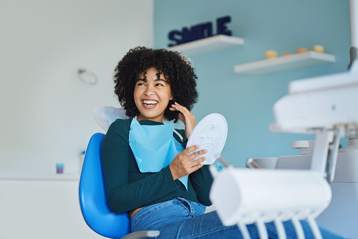 Shot of a young woman admiring her teeth after having a dental procedure done