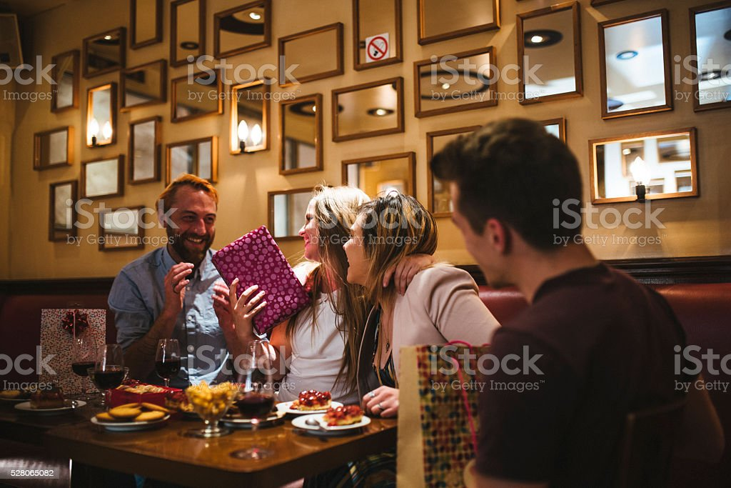 Friends celebrating birthday in a restaurant. Woman who is having a...